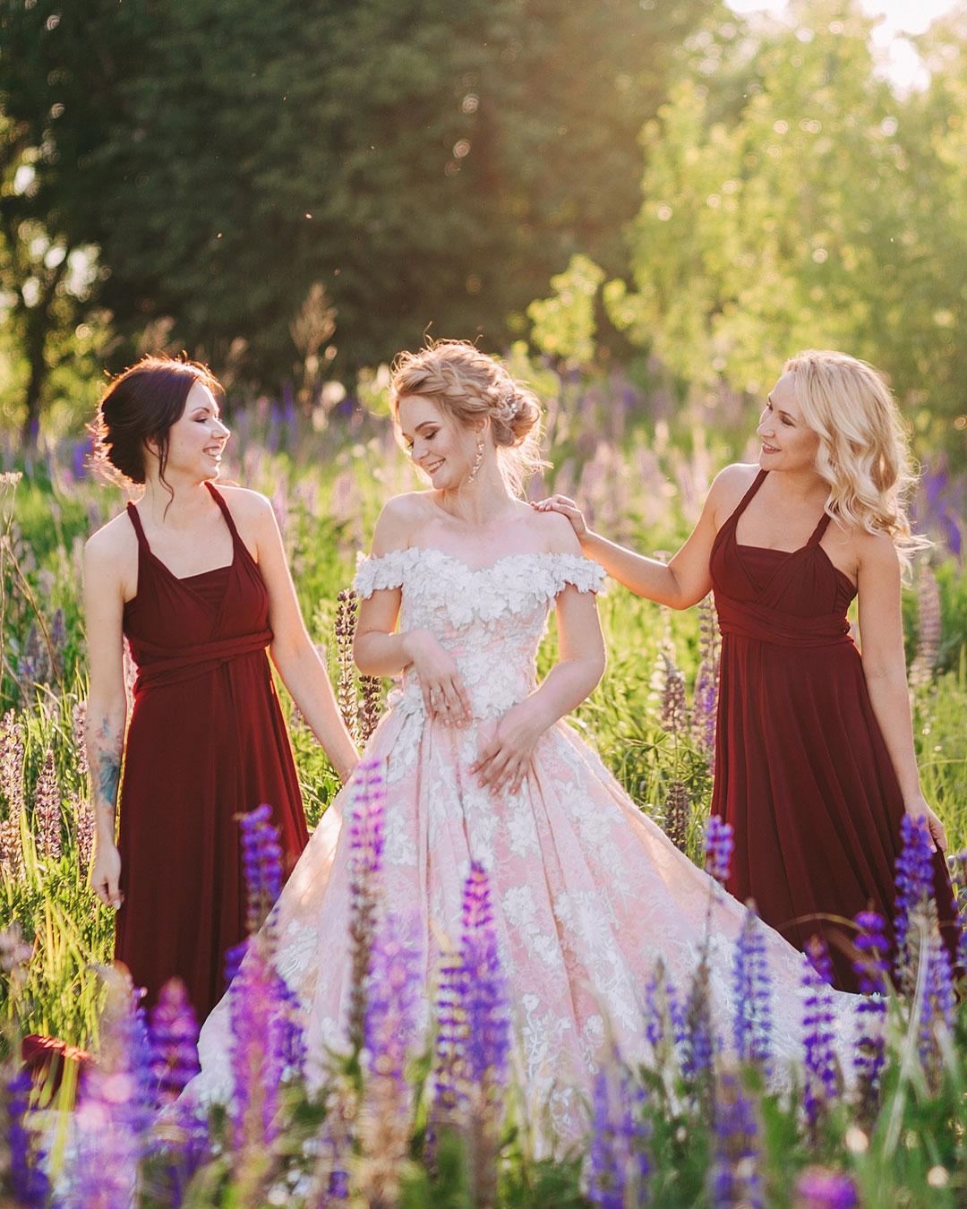 Подружки невесты в бордовых платьях на поле с люпинами