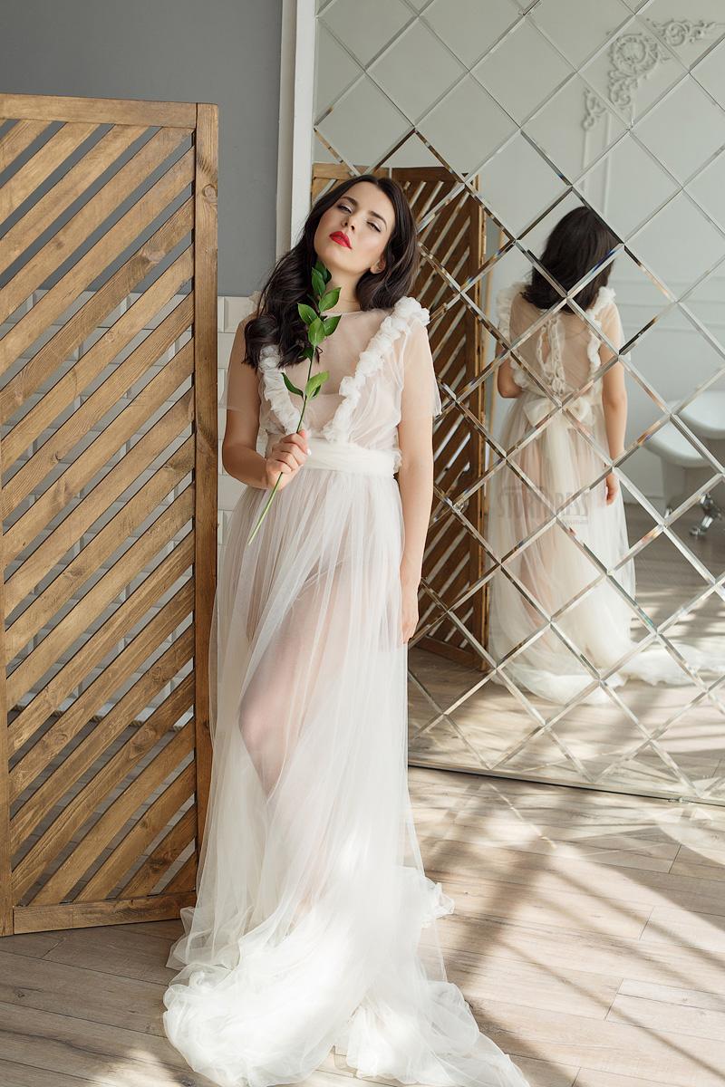 Девушка в белом будуарном платье возле зеркала