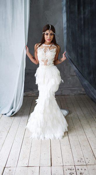 Девушка в белом платье из перьев с жемчужным украшением