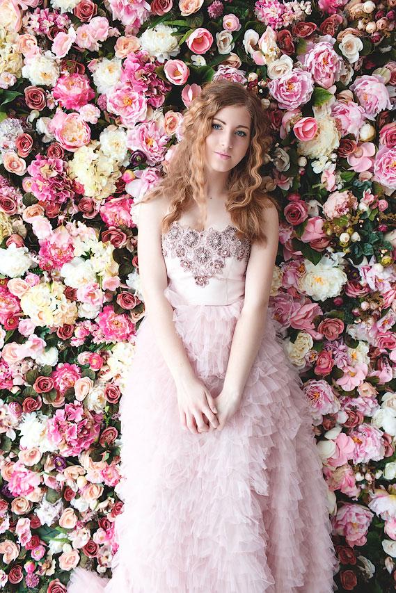 Юная нежная девушка в окружении сотни прекрасных цветов
