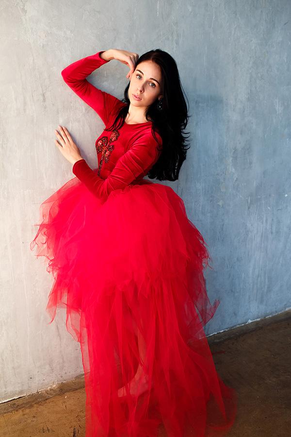 Студийная фотосессия с простым интерьером в красном фатиновом платье