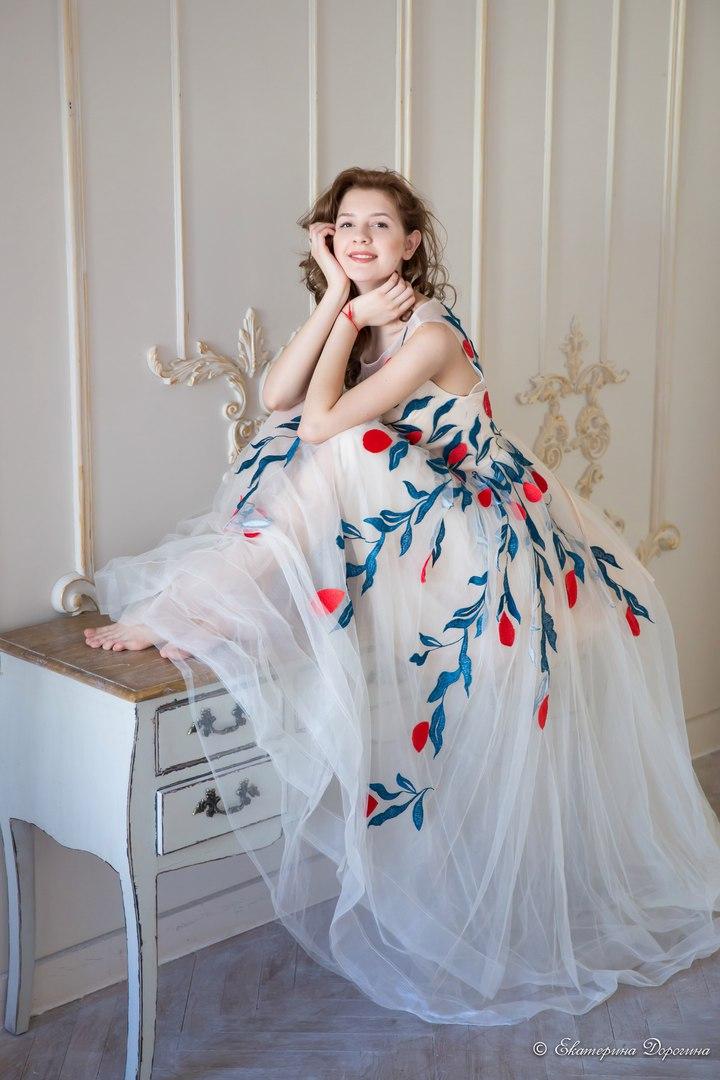 Юная модель в расшитом яркими цветами платье