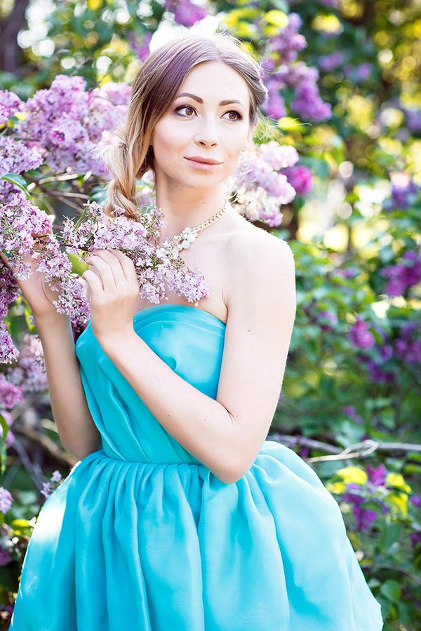 Девушка в голубом платье на фоне сирени
