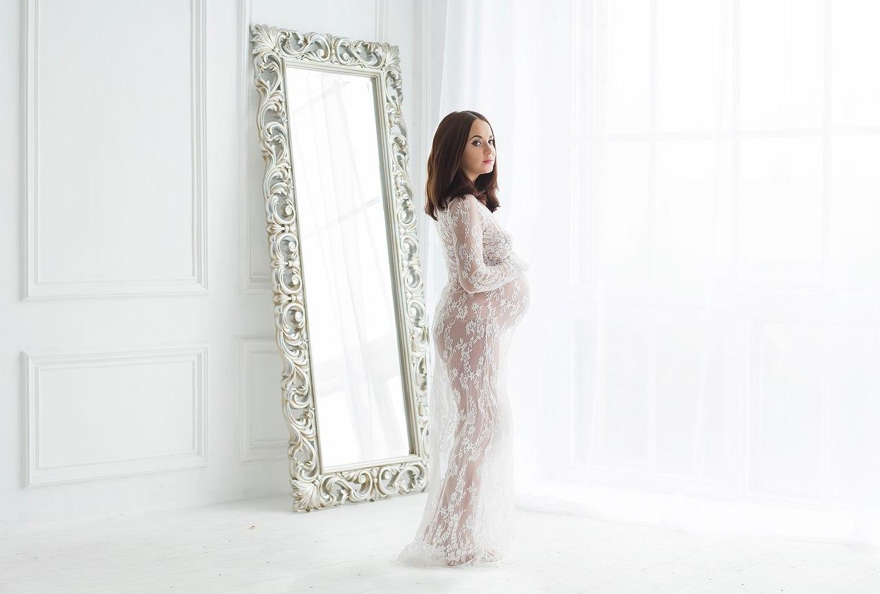 Фото беременности в белой студии с зеркалом