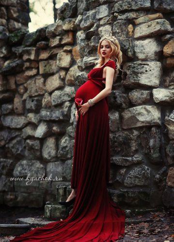 Беременная девушка в красном платье на фоне каменной стены