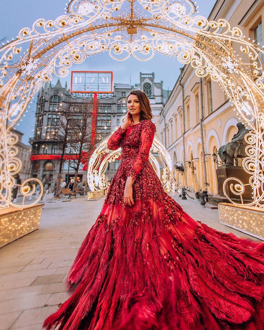 Девушка в красном платье с перьями на фоне ЦУМа