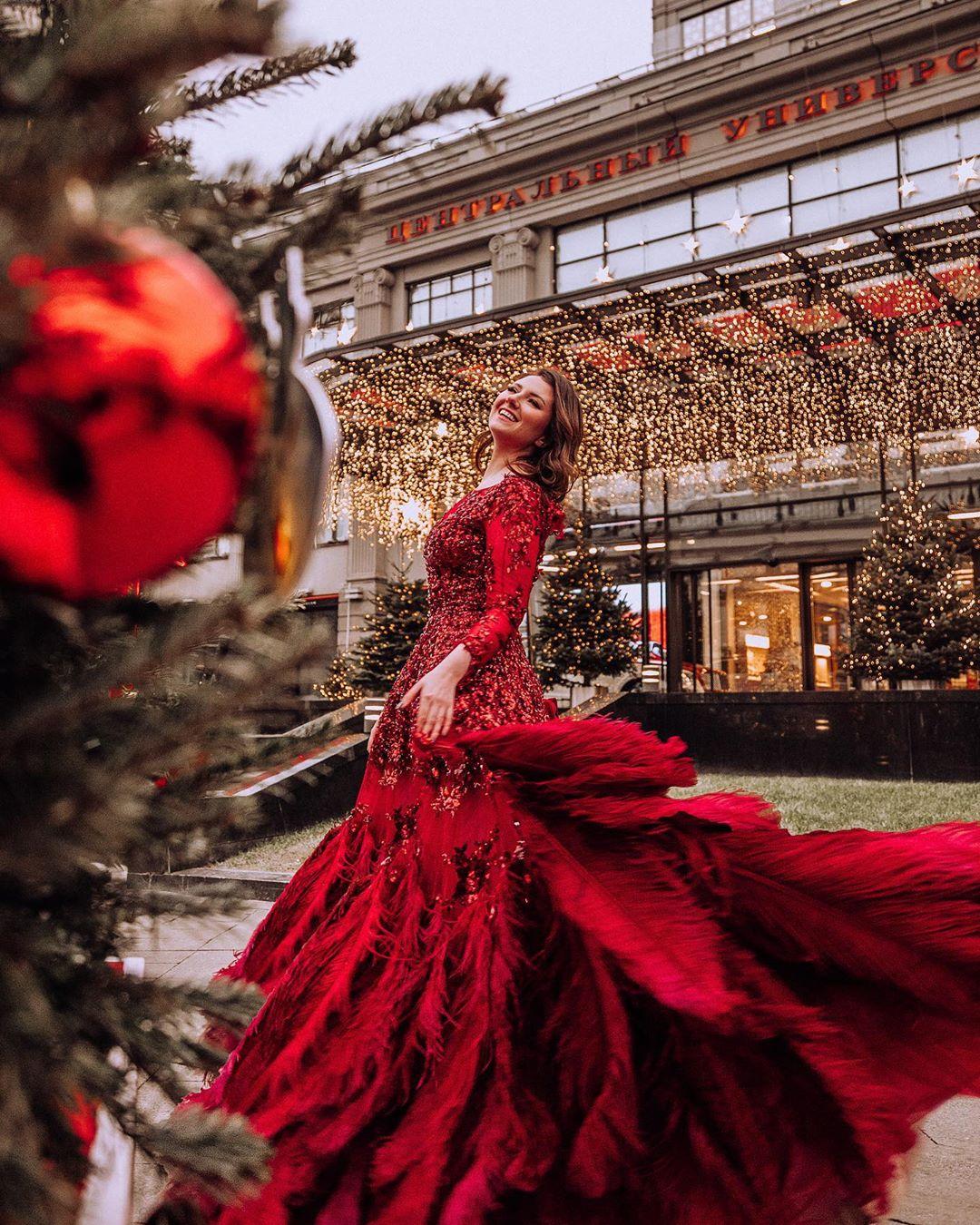Девушка танцует в красном платье с перьями на фоне гирлянд ЦУМа